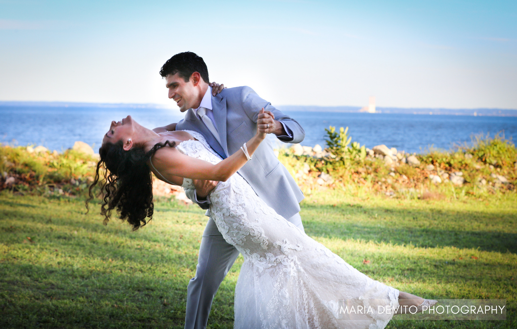 Bride and groom smiling in happy embrace on lawn in front of ocean backdrop.