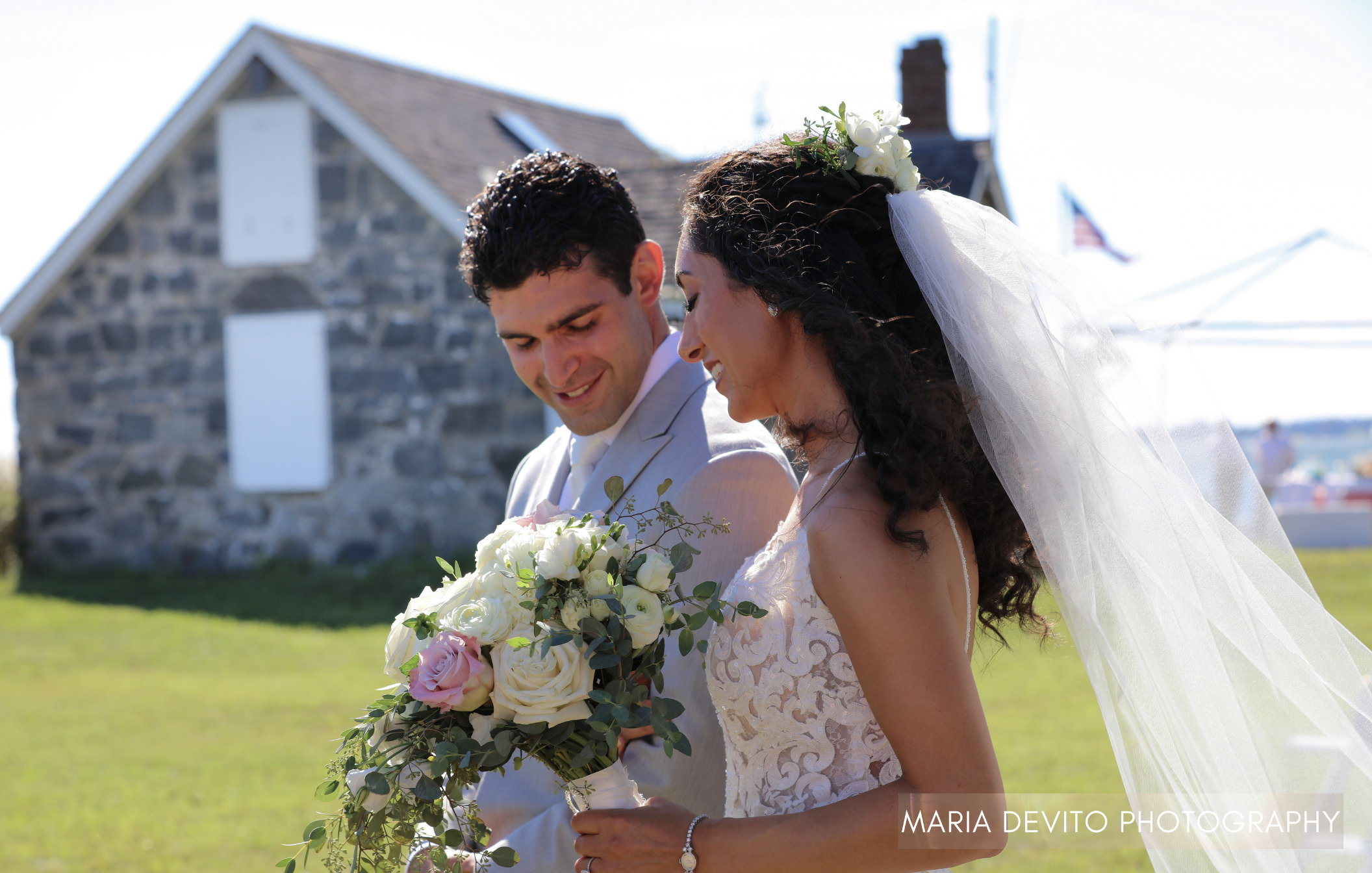 Bride and groom holding gorgeous bouquet in front of a stone building with veil trailing in the wind