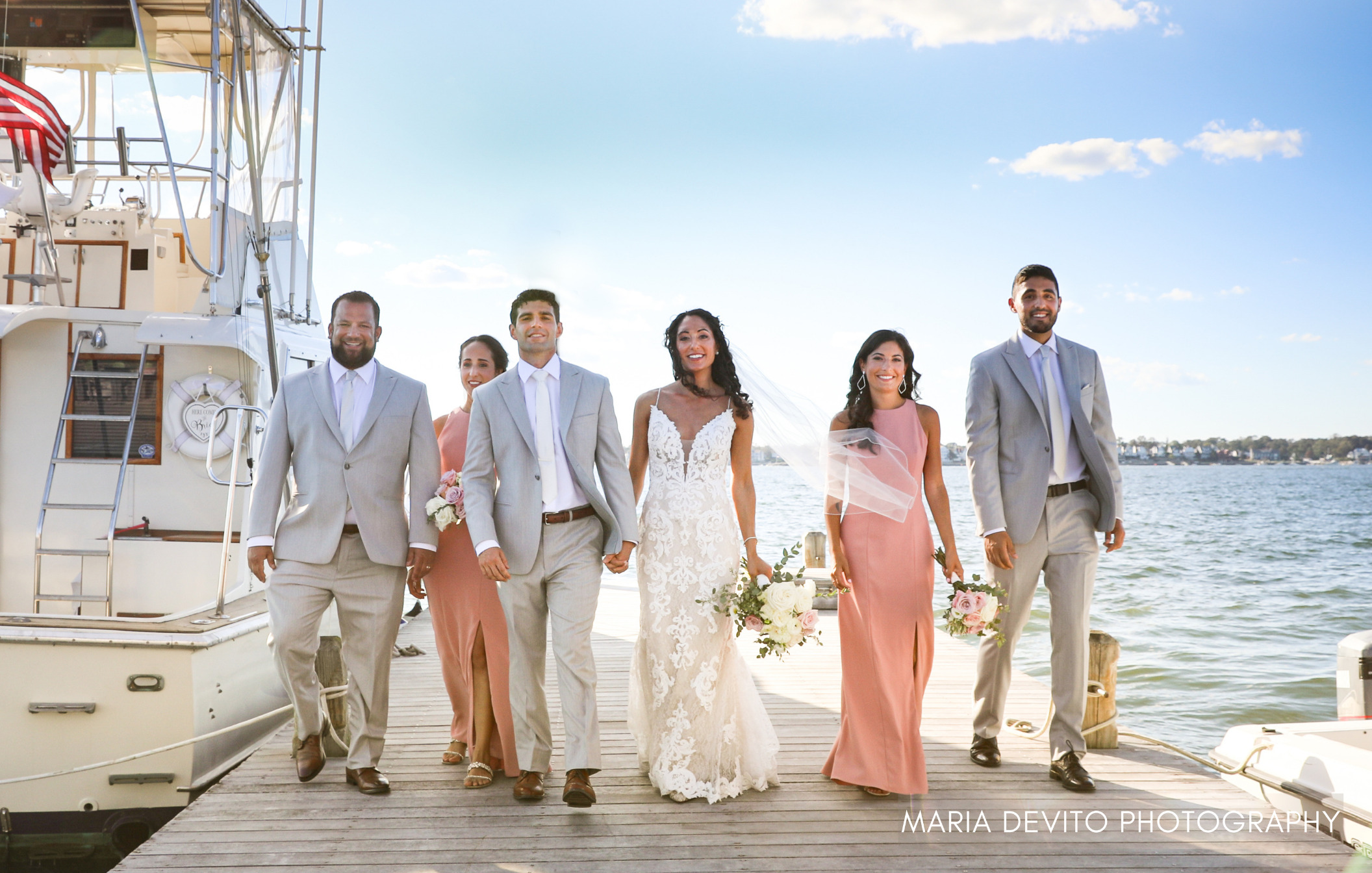 Wedding party walking towards camera on dock next to boat with water in background. Bridesmaids are holding bouquets.