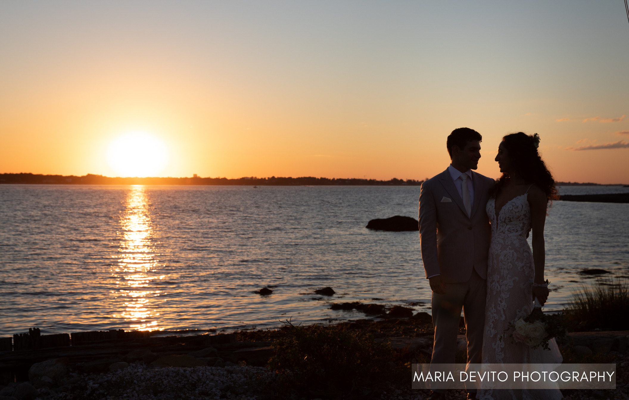 Bride and groom holding eyes while embracing in front of ocean sunset during golden hour