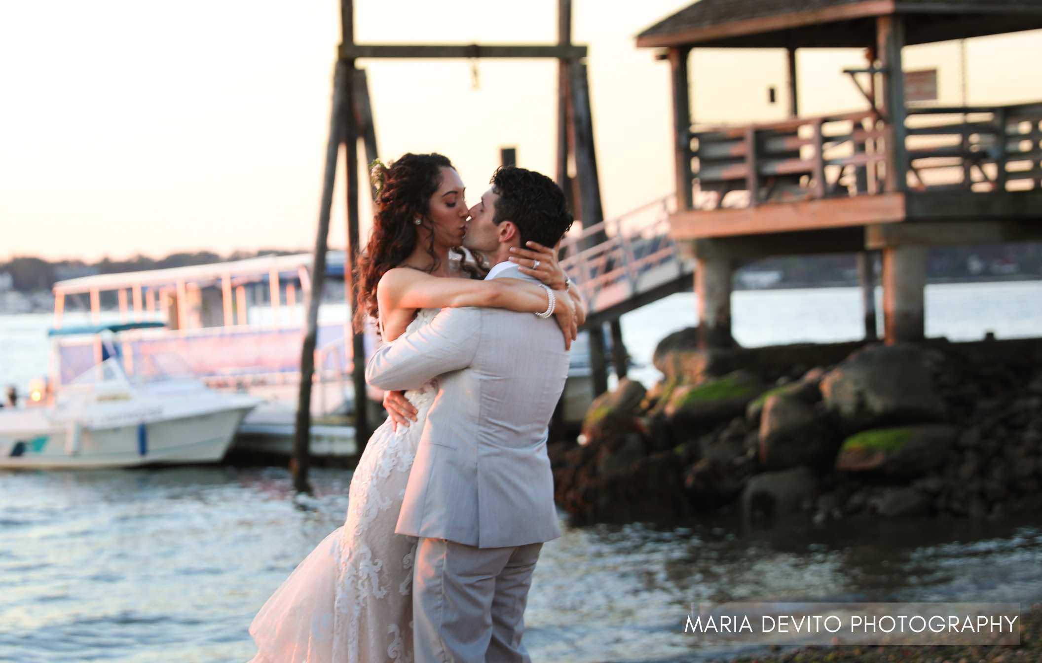 Groom holding up bride while they kiss in front of ocean backdrop with docked boat during wedding.