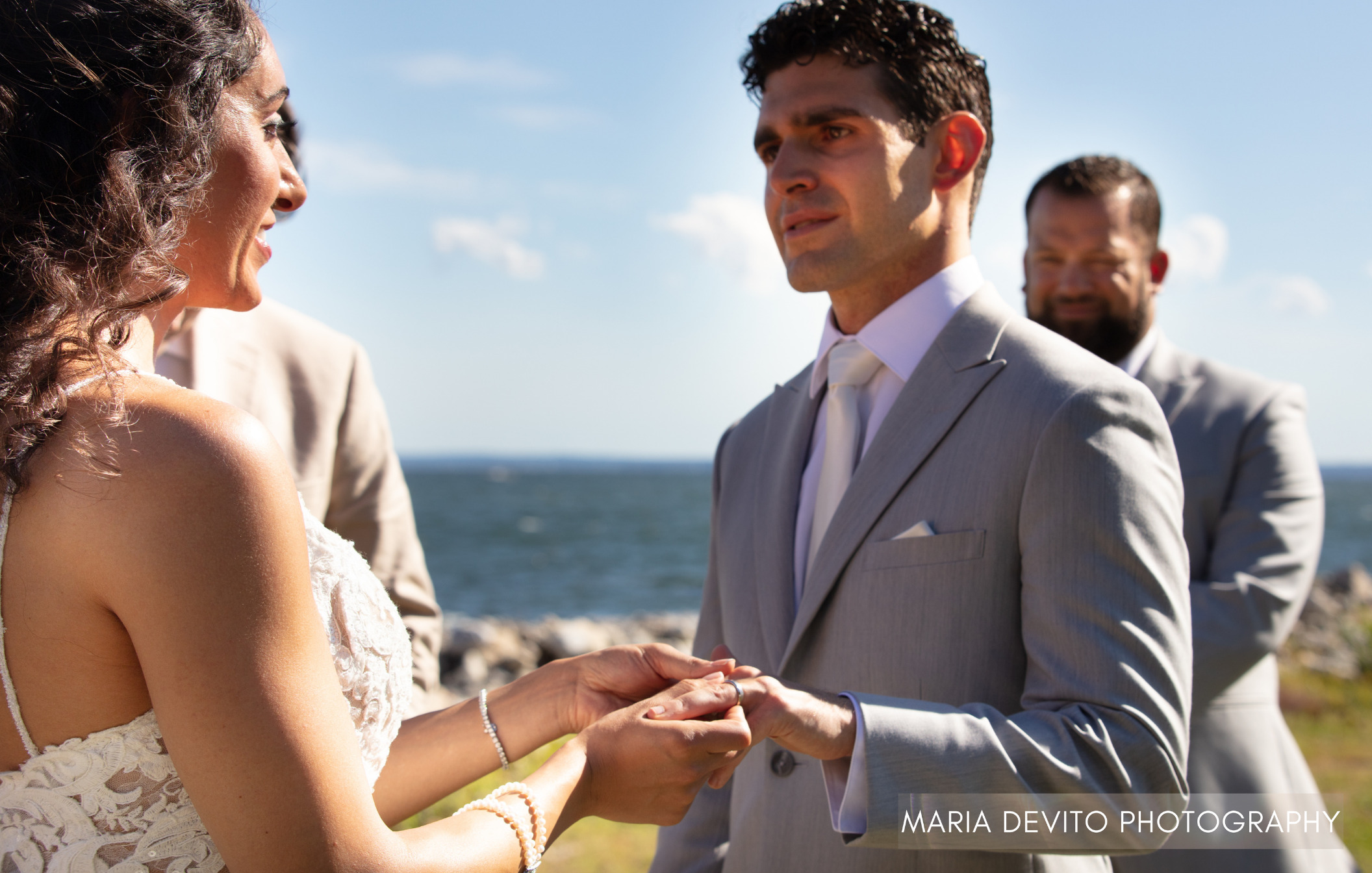Bride and groom holding hands during wedding ceremony, saying their vows with officiant and groomsman in background with ocean backdrop.