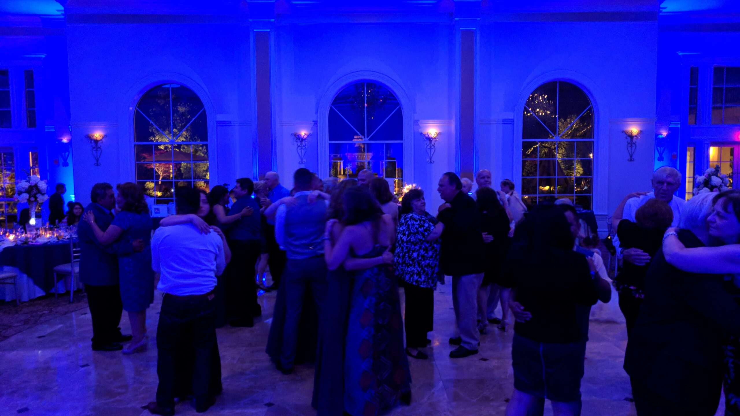 Blue lit dance floor with couples slow dancing at Aria wedding