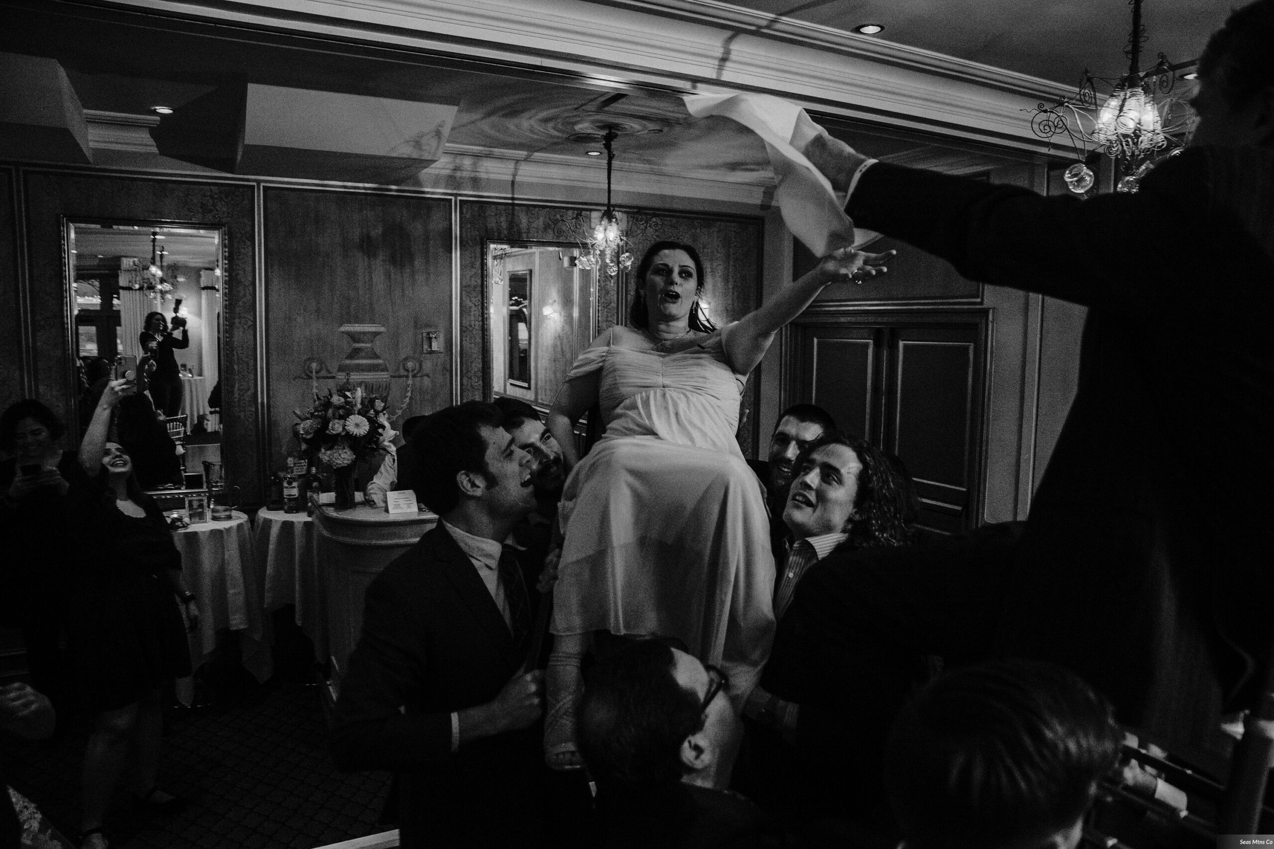 Bride and Groom held up on chairs during hora on dancefloor at Lescale wedding in Greenwich CT