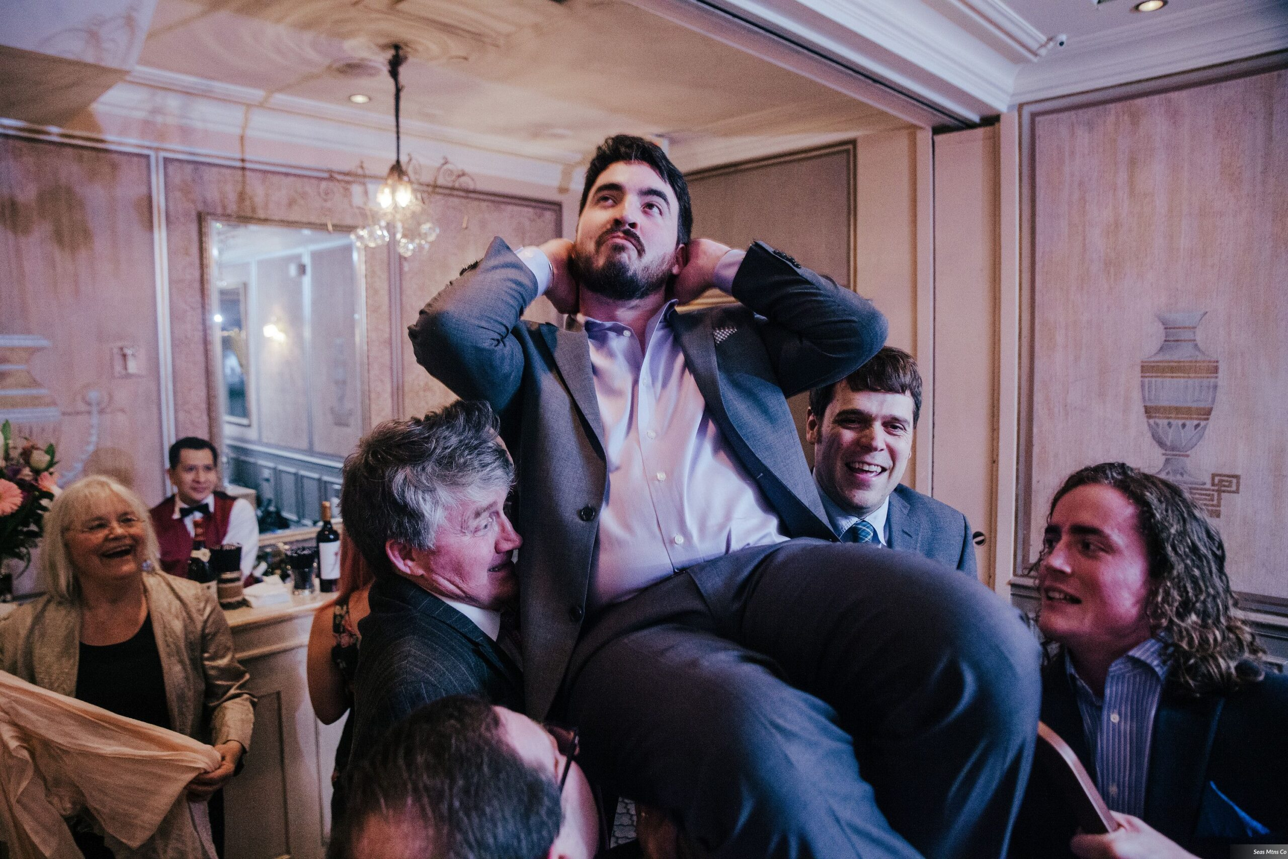 Groomsman held up on chair during hora at wedding at Lescale in Greenwich CT