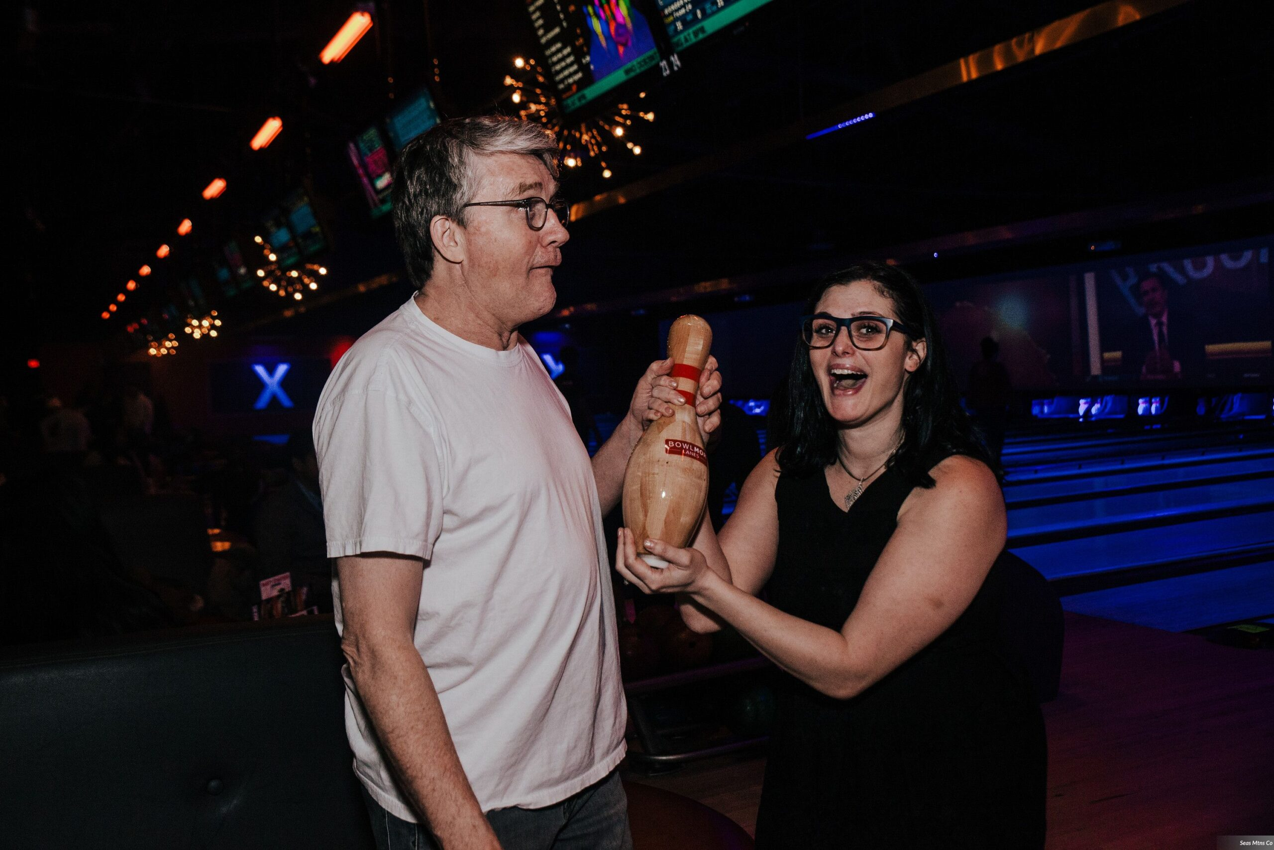 Bride and Groom making funny faces holding bowling pin at Bowlmor Lanes during afterparty of wedding