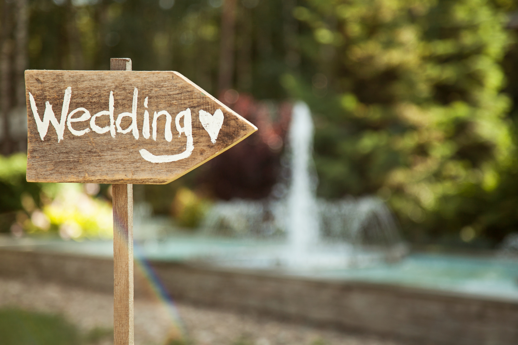 Wedding decor, Wooden plaque with white text spelling Wedding with fountain in background at Riverview Bistro Wedding