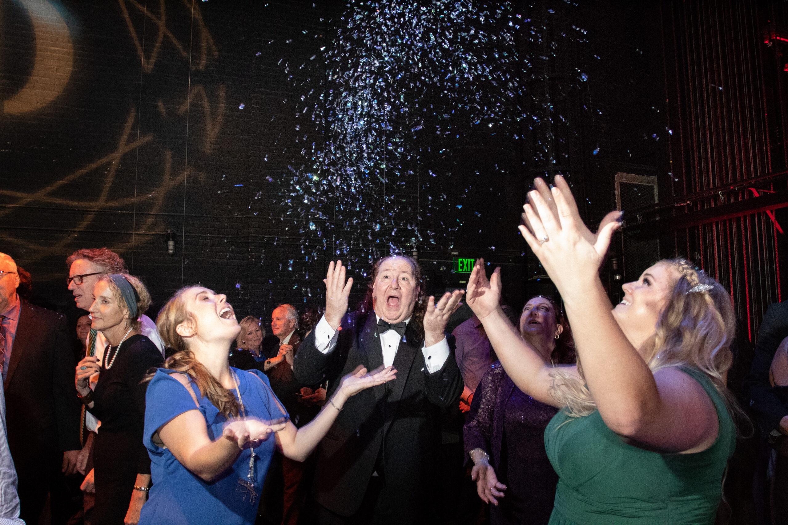 Happy wedding guests on dance floor throwing up confetti