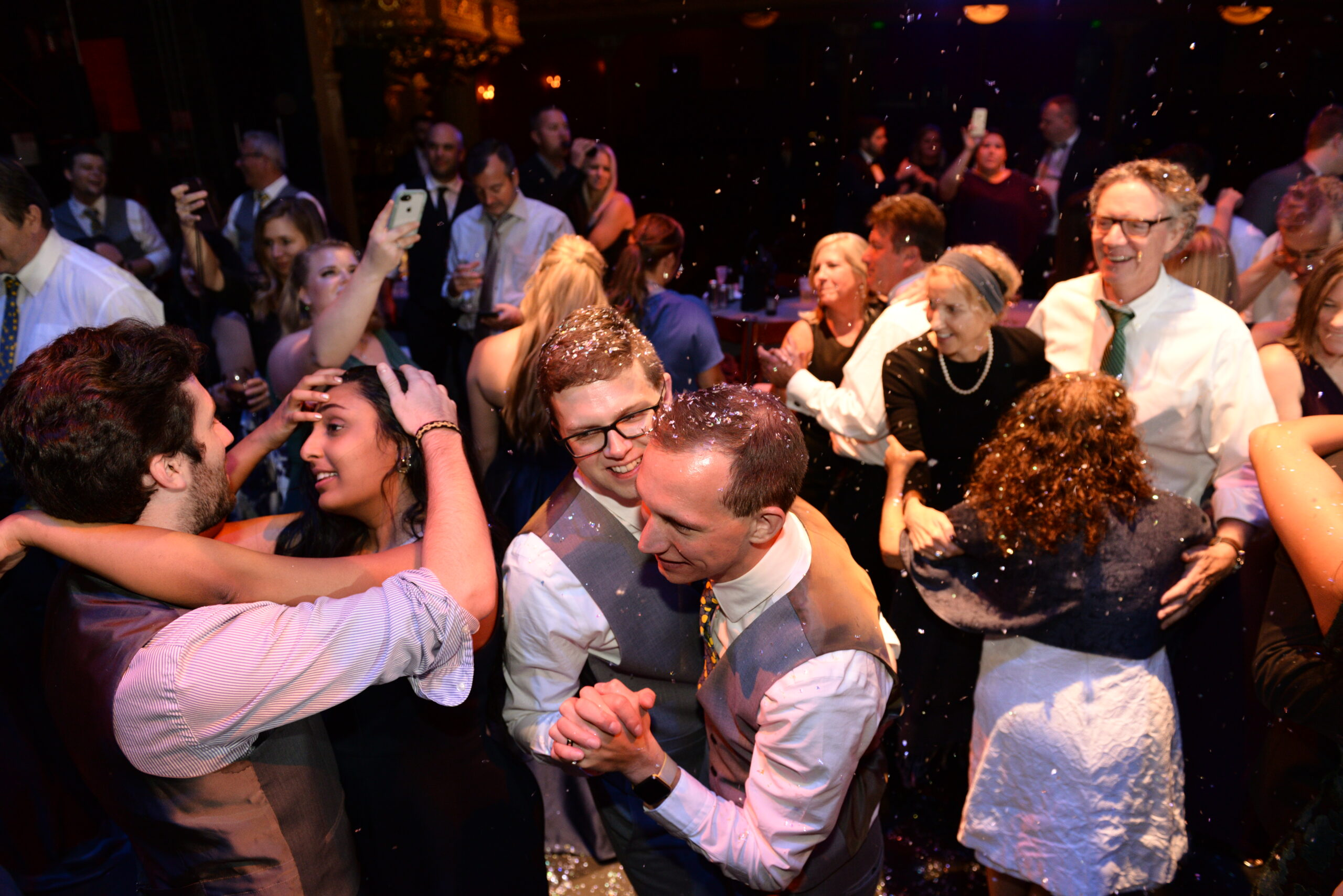 Groooms on dancefloor with happy guests and confetti at The Colonial Theatre