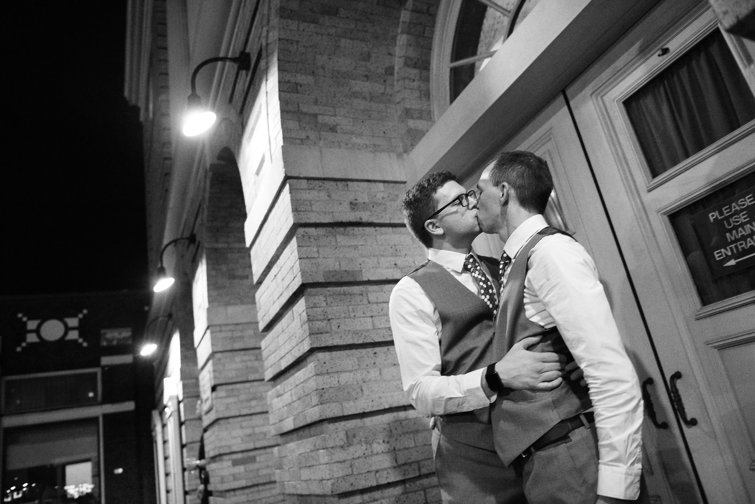 Grooms kissing in front of The Colonial Theatre black and white