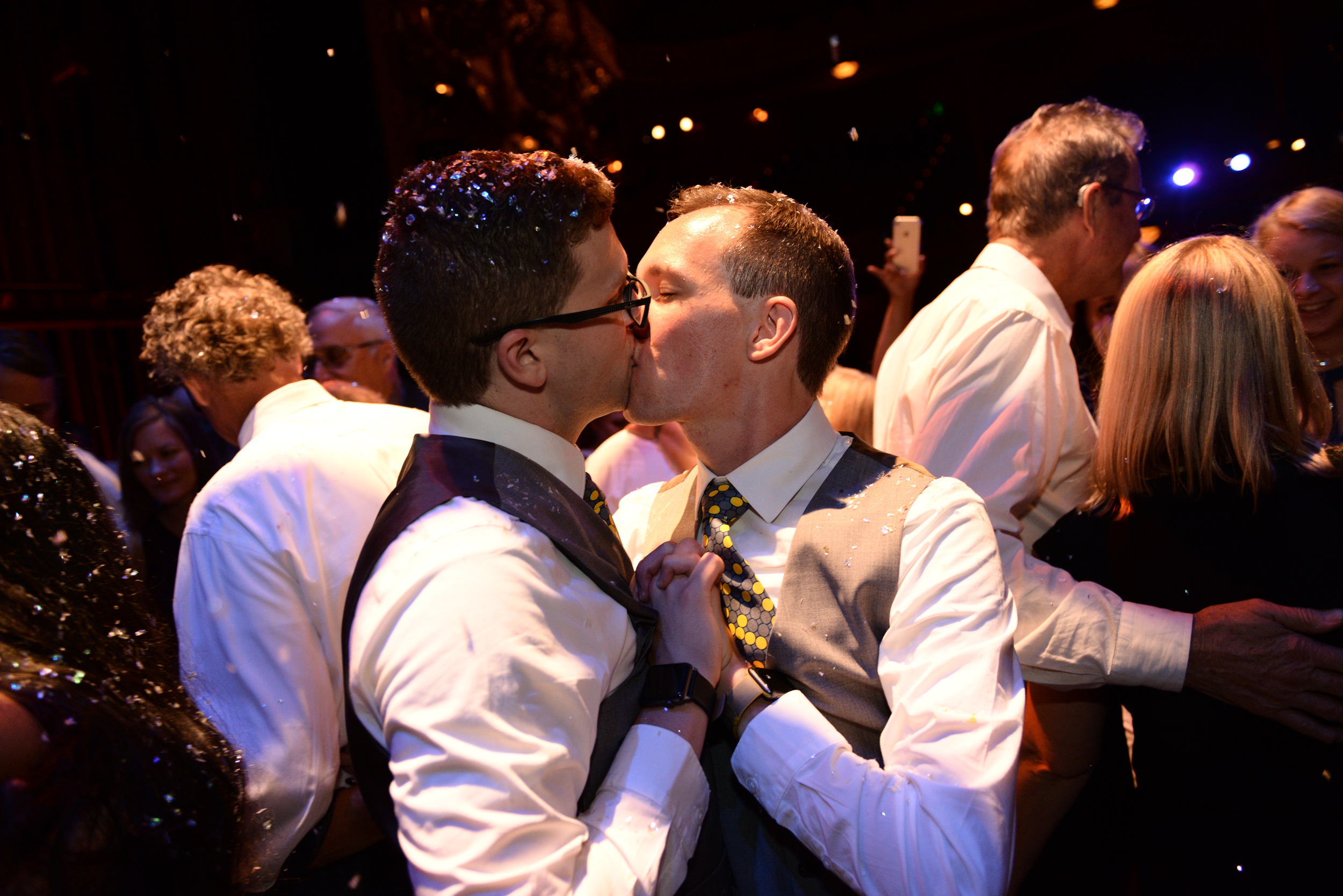 Grooms kissing under confetti on wedding dancefloor at The Colonial Theatre