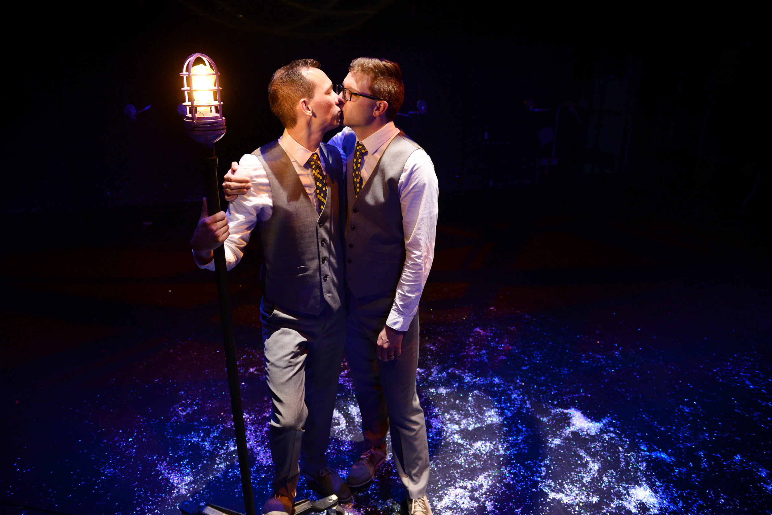 Grooms kissing holding lamp-post after wedding with glittering confetti on the ground