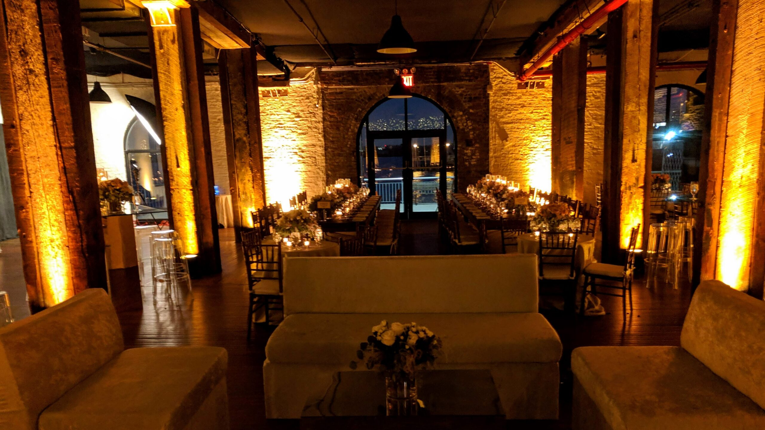 Lounge seating for cocktail hour with uplighting at rustic wedding venue Liberty Warehouse Brooklyn NY
