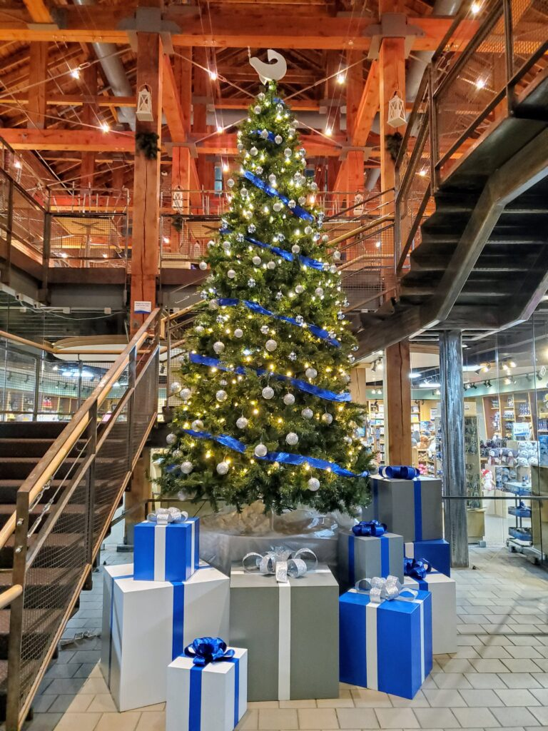 Maritime Aquarium Holiday Parties Christmas Tree with Gifts next to stairway in Norwalk