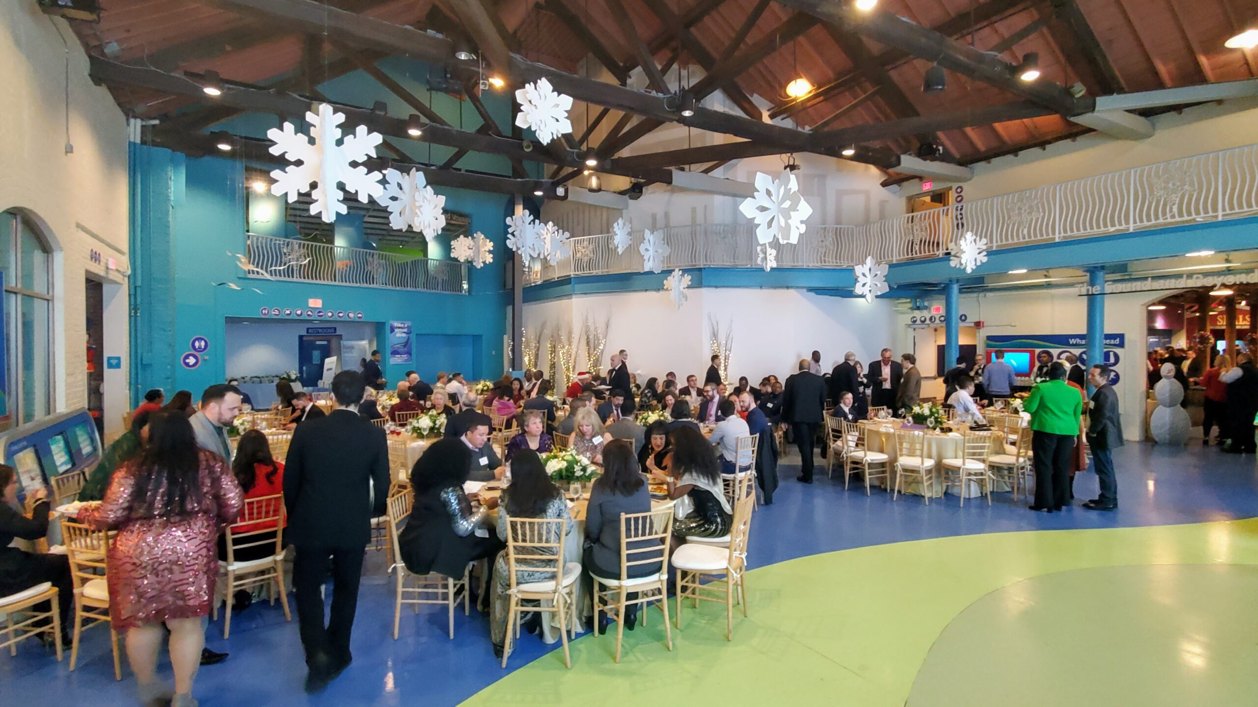 Corporatate holiday party at the Maritime Aquarium showing guests seated for dinner at tables in reception hall