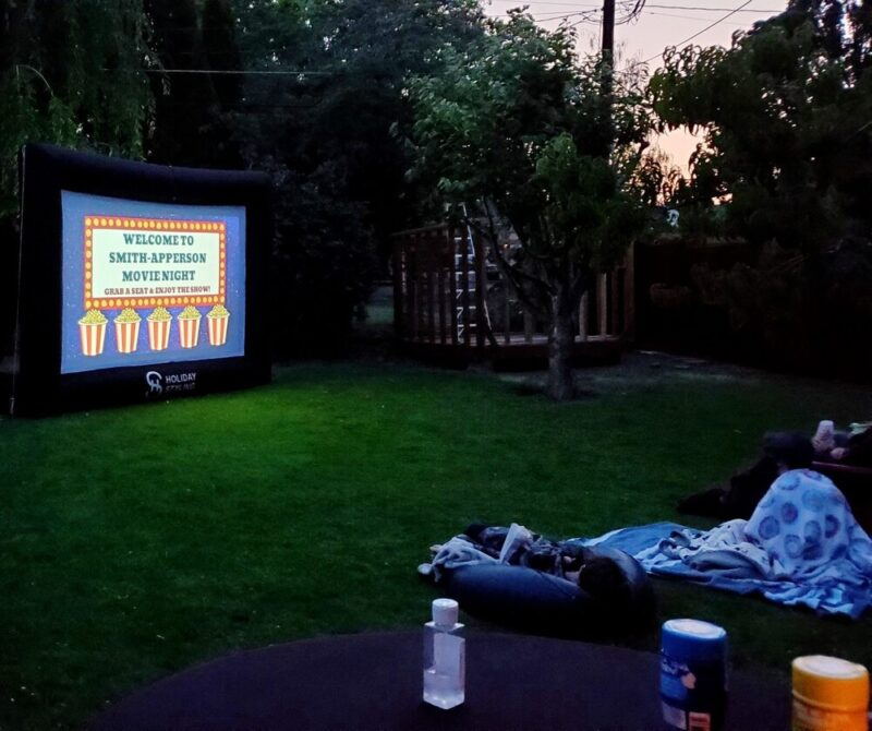 Family watching outdoor movie in backyard under trees on grass