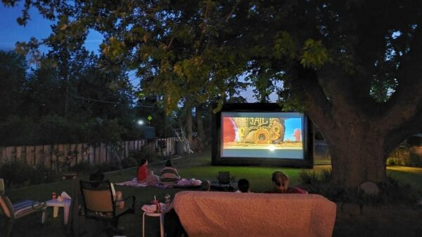 Outdoor movie night with projection screen and big tree
